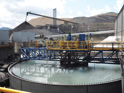 One of the mine's two Delkor thickeners dewaters magnetite concentrate and another handles tailings. In the background, lean ore is crushed, then stockpiled for blending with higher-grade ore from the pit.